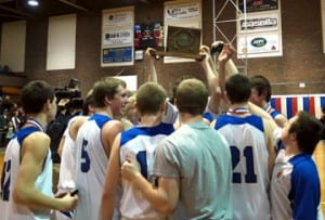 The members of the Williamstown Boys basketball team hold the Div. III championship trophy aloft following their 76-65 victory over Rivendell last Saturday night at the Barre Auditorium. Williamstown's Blue Devil Boys have now won four straight Div. III State Championships. Photo by Bill Croney.