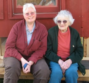 Home sharer Janis (left) and her home provider, Dorothy, enjoy a nice day in front of their new chicken coop in Wells River.