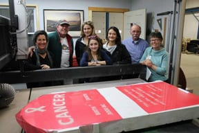 From L-R: Susan Walker, Randy Walker, Tori Biondolili, Emily Boisvert (in front), Josselyne Blakley, George Clain and Theresa Lever checked out the headstone donated by Scott Hutchins and inscribed by Randy and Sue Walker of Family Memorials that will be used for next month's Bury Cancer Parade in Barre.
