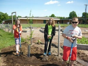Stella Cannizzaro, Grace Moustakas and Kaden Giroux help plant a mulberry tree as part of the garden at Berlin Elementary School.