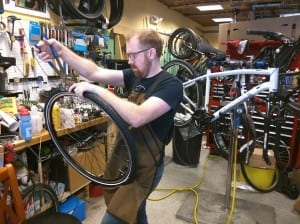 Vermont Bicycle Shop owner Darren Ohl works on repairing a tire for a customer. Since opening in April, Ohl has been pleased with the amount of business as he continues to build community through his shop's offerings.